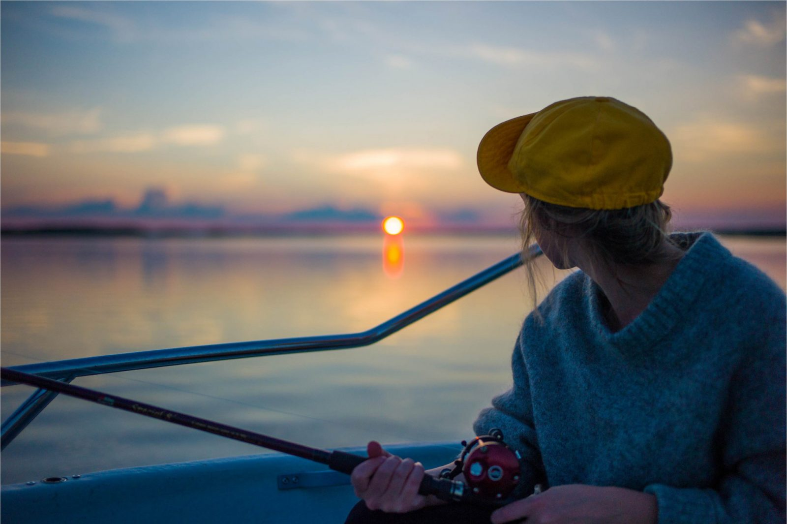 Girl fishing on a boat in the sun rise