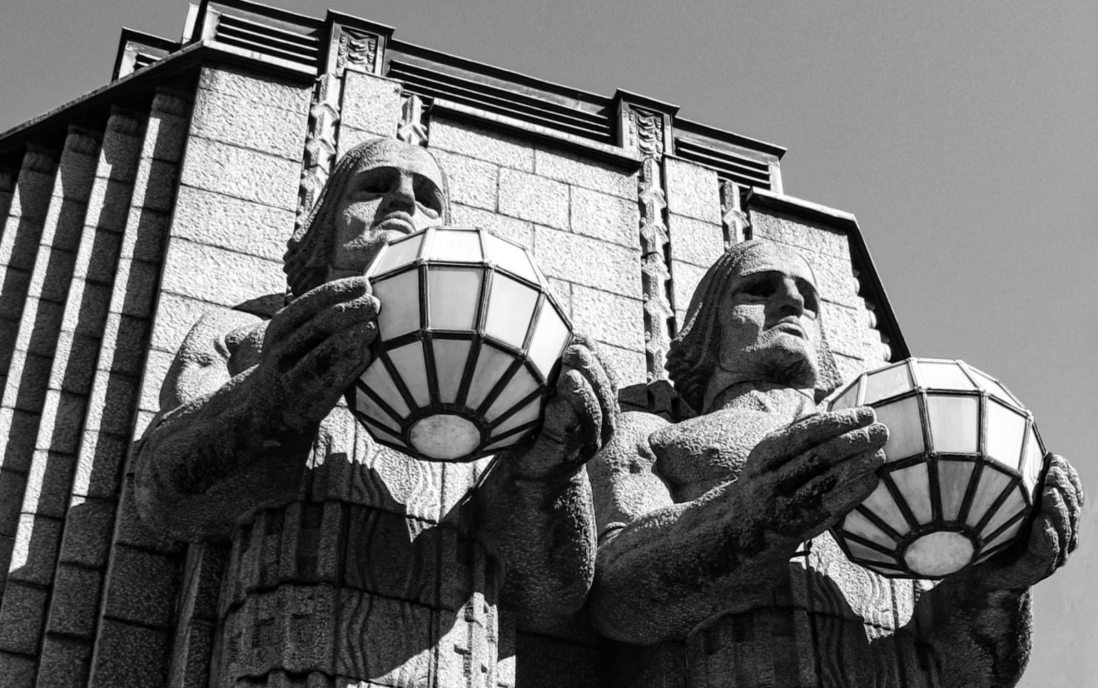 Stenstatyer, män i sten som håller i ljusglober