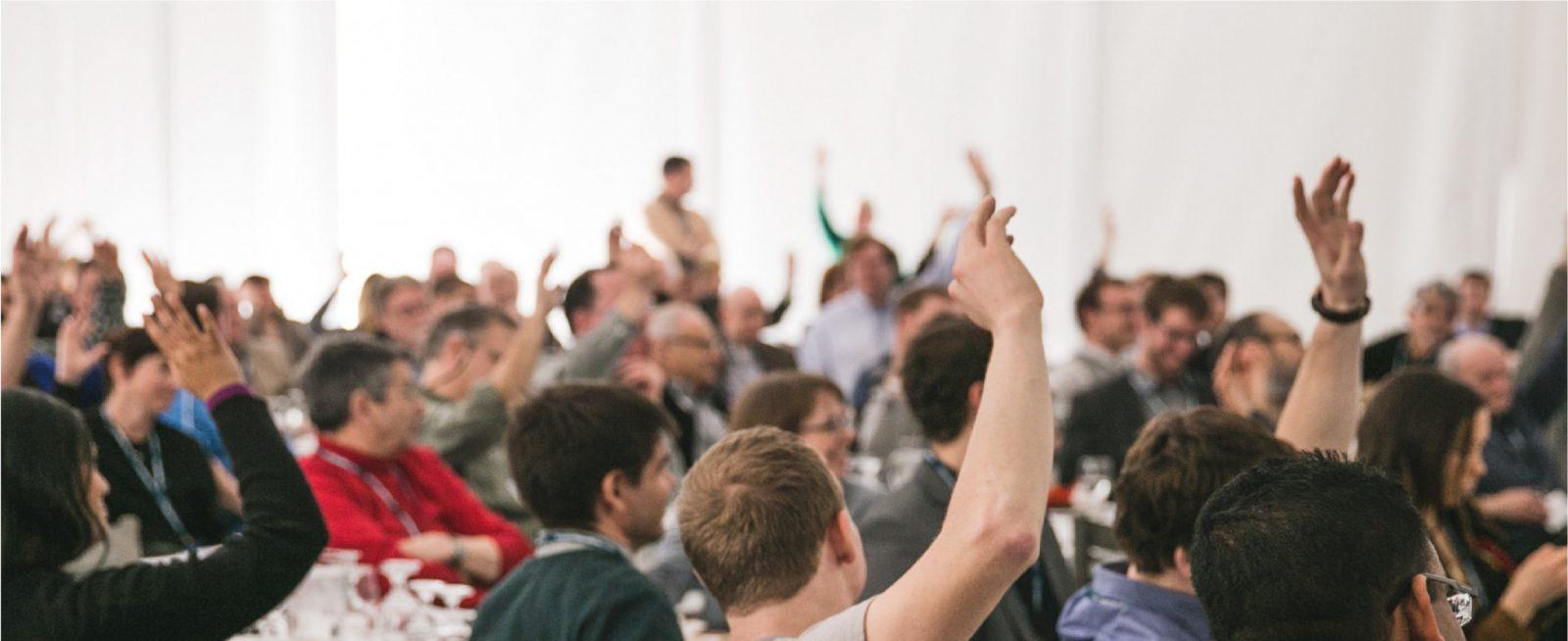 People at meeting raising hands