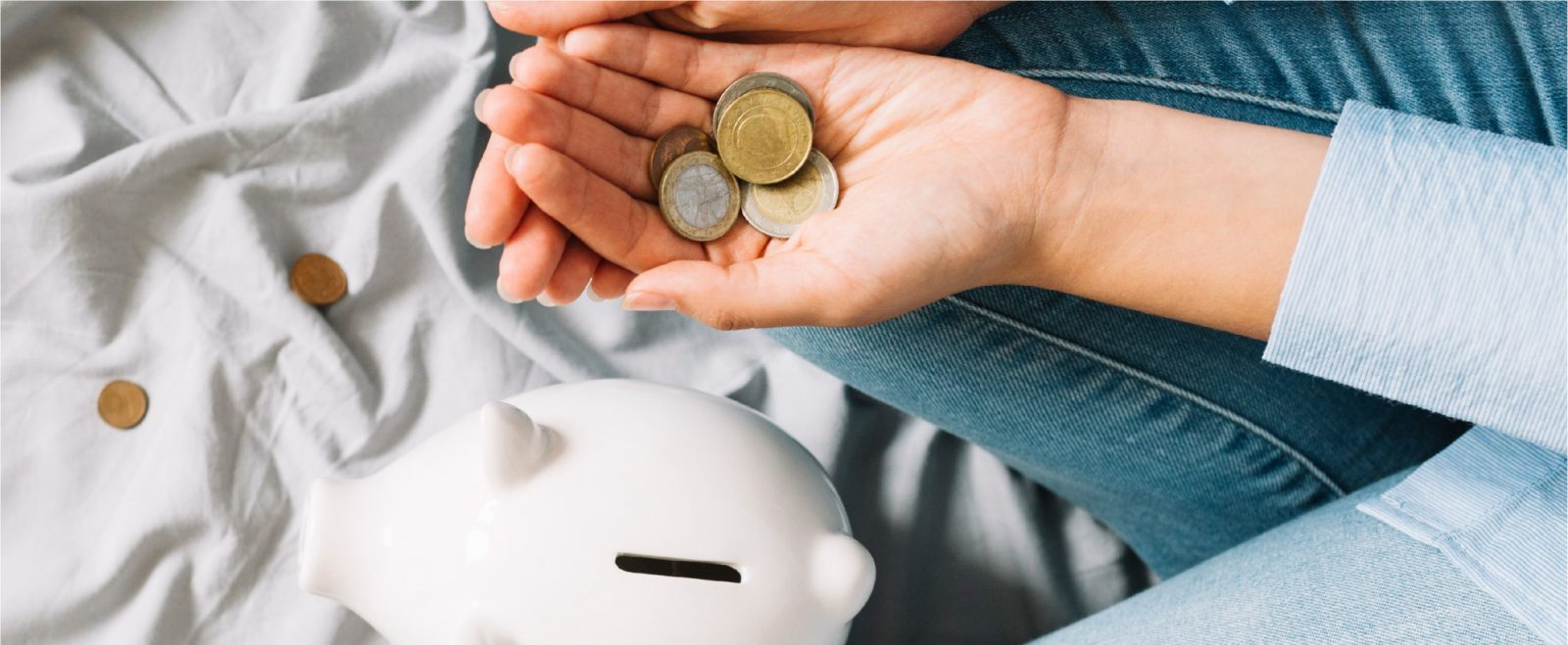 Women holding coins in hand and a piggy bank